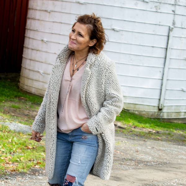 Liz walking in front of barn silo