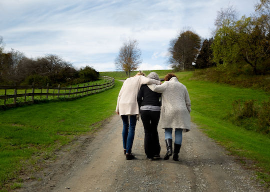 Three women walking and consoling