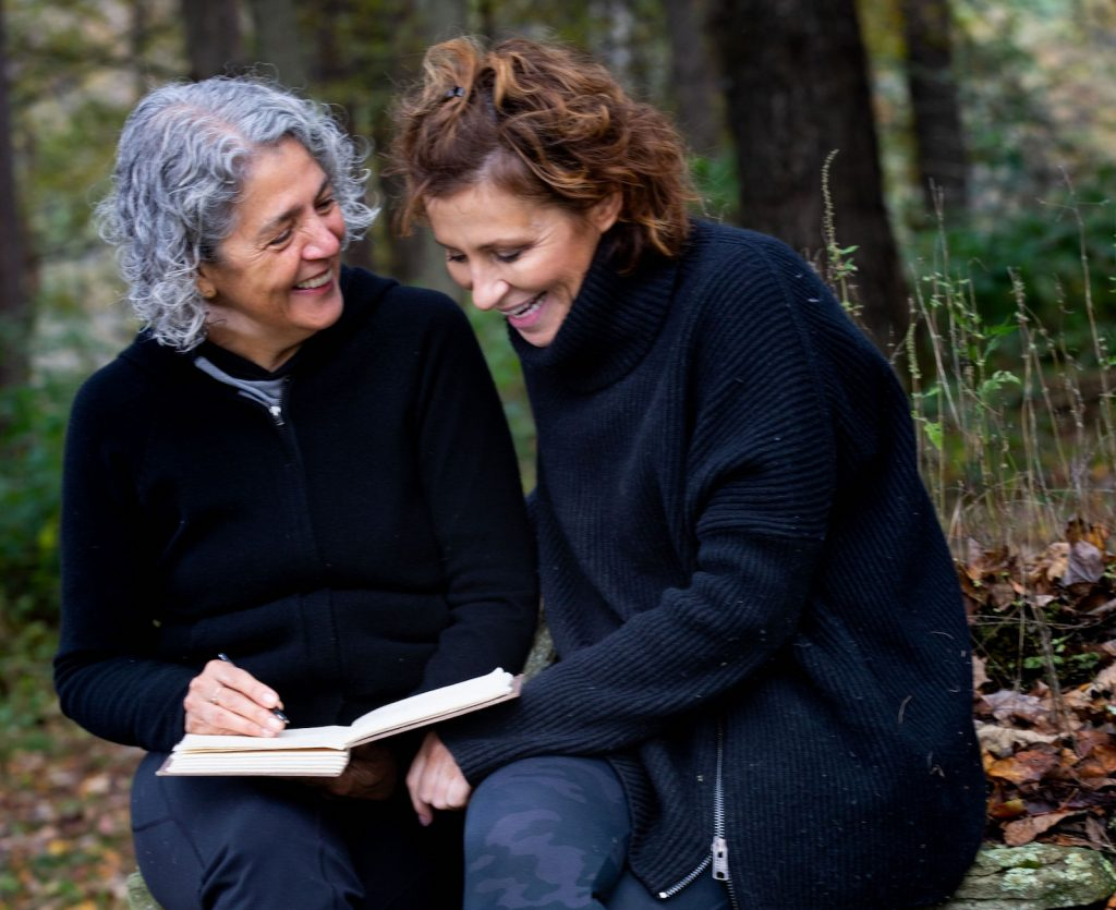 Two women smiling in woods with book